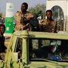 Des soldats soudanais à bord d'un véhicule de l'armée alors qu'ils traversent le complexe du ministère de la Défense à Khartoum.