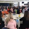 Des personnes en discussions autour de plusieurs tables rondes dans une salle.