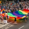 Des gens se promènent avec un immense drapeau arc-en-ciel devant une foule.