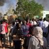 Plusieurs personnes marchent dans une rue de Khartoum. On voit au loin une colonne de fumée noire.