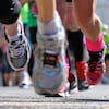 Photo générique, des souliers de coureurs et des coureurs en arrière-plan