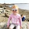 Une petite fille rousse est assise sur un rocher à la plage, porte des lunettes de soleil en forme de coeur et sourit pour l'appareil-photo.