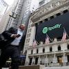 Un piéton passe devant la façade de la Bourse de New York aux couleurs de l'entreprise Spotify.