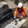 Une archéologue portant un casque et une tenue de travail fluorescente disposant les os d'une dépouille sur une bâche à côté d'un cercueil déterré.