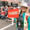 Devant une foule, une dame sourit à la caméra, portant un chapeau de cowboy et en tenant un ensigne qui est écrit YAHOO!