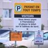 Dans le stationnement d'un hôpital, où se trouvent des automobiles, une pancarte indique : « Stationnement payant en tout temps ».