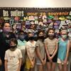 Des élèves se trouvent devant un babillard où l'on retrouve des souliers colorés.