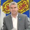 Stephen McNeil, assis et souriant, devant trois drapeaux de la Nouvelle-Écosse.
