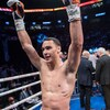 Il lève les poings en l'air après une victoire.