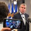 Stephen McNeil se tient devant des micros, des caméras et le drapeau de la Nouvelle-Écosse lors d'une conférence de presse.