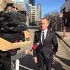 Stockwell Day debout à l'extérieur en entrevue avec la caméra de télévision en avant-plan.