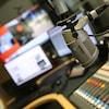 Un micro dans un studio de radio avec des écrans et une console en arrière plan.
