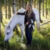 Sue McIntosh pose avec son cheval Finnegan, qui broute l'herbe au milieu des arbres.