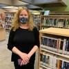Une femme portant le masque sanitaire dans une bibliothèque.