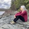 Suzanne Trudel est assise sur un rocher près d'un forêt.