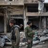 Deux hommes armés se tiennent debout, dos à dos, dans les décombres d'un bâtiment.