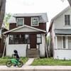 Un petit garçon passe en vélo devant une maison blanche et brune.