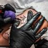 Un tatoueur dessine une abeille sur le bras d'une femme.