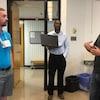 Trois hommes discutent dans une salle de classe, l'un porte le protoype autour du cou.