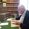 Ted Hughes assis à une table en train de feuilleter un livre dans la bibliothèque du palais de justice de Victoria.