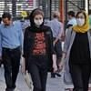 Des femmes et des hommes, dont certains portent des masques de protection, circulent  dans une de la capitale iranienne.