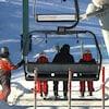 Un homme et deux enfants s'assoient dans un télésiège. Un opérateur se retrouve à côté d'eux.