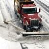 Un chasse-neige dégage une rue enneigée.