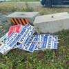 Des pancartes électorales sont empilées pêle-mêle près de blocs de ciment, dans un terrain vague.