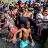 Une foule de migrants qui se baignent dans un lac.