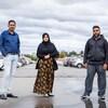 Trois personnes se tiennent debout dans un stationnement.
