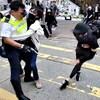 Vêtu de noir et masqué, le manifestant se tient l'abdomen, alors que deux autres protestataires s'attaquent à l'agent de police.