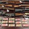 17 fusils et des liasses de billets de 50 $ et de 100 $ étalés sur une table.