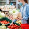 Une femme prend une tomate dans une épicerie.
