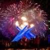 Des gens regardent les feux d'artifice et la torche olympique.