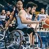 Il dribble le ballon pendant un match de basketball en fauteuil roulant.