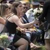 Une jeune femme en robe noire prend un bouquet de roses blanches.