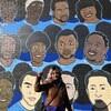 Toshira Garroway devant un mur peint sur lequel on peut voir des visages.