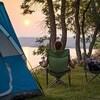 Un couple de campeurs sont assis sur des chaises au bord d'un lac peu avant le coucher de soleil