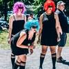 Trois femmes jouent en extérieur à la pétanque. Toutes les trois portent des perruques de couleur rouge, fuchsia et bleu, des lunettes de soleil et une robe noire.