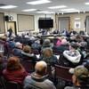 Des citoyens assis à une réunion du conseil municipal.