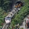 Des équipes de secouristes s'activent autour du site où le train a déraillé, à la sortie d'un tunnel dans les montagnes de Hualien.