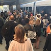 Des personnes se pressent pour monter à bord du train léger.