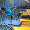 Un homme fait un saut dans un centre de trampoline.
