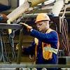 Un travailleur manipule un cadre en acier.