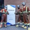 Trois travailleurs prennent fièrement la pose avec leurs pouces levés devant une affiche de la compagnie NORCAT.