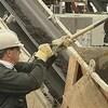 Un travailleur qui met du charbon dans une benne à l'aide de sa pelle.