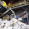 Une machine qui tri du papier. À l'avant, on trouve une immense quantité de papier.