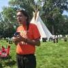 Tristen Durocher est debout devant son tipi avec une tasse dans les mains.