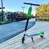 Photo d'une trottinette noire et verte stationnée sur un plancher de bois
