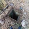 Un trou de forme carrée sur un terrain de paille.